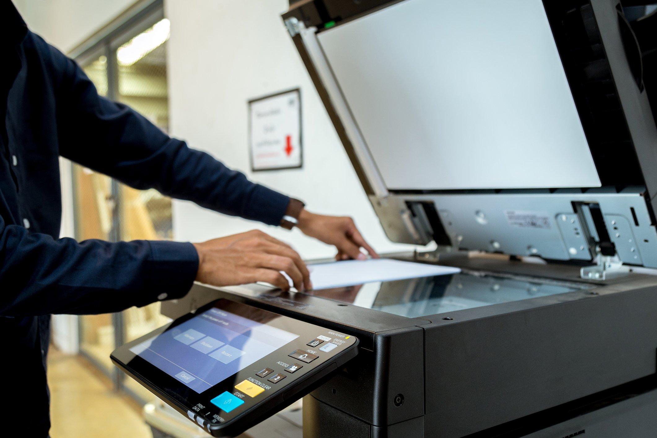 Businessman using multifunction printer (MFP)