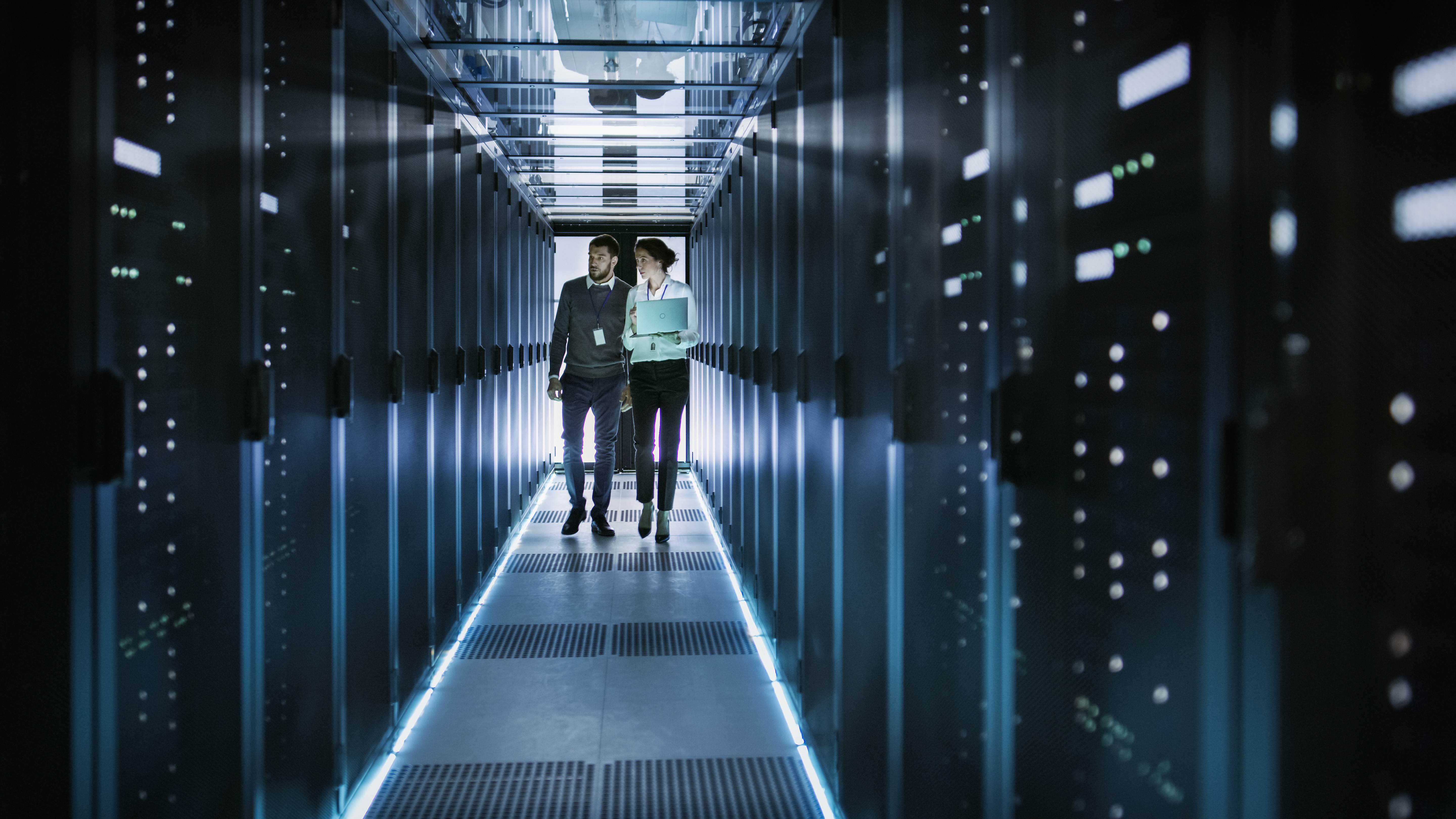 IT businessman and businesswoman walking through servers in a data center